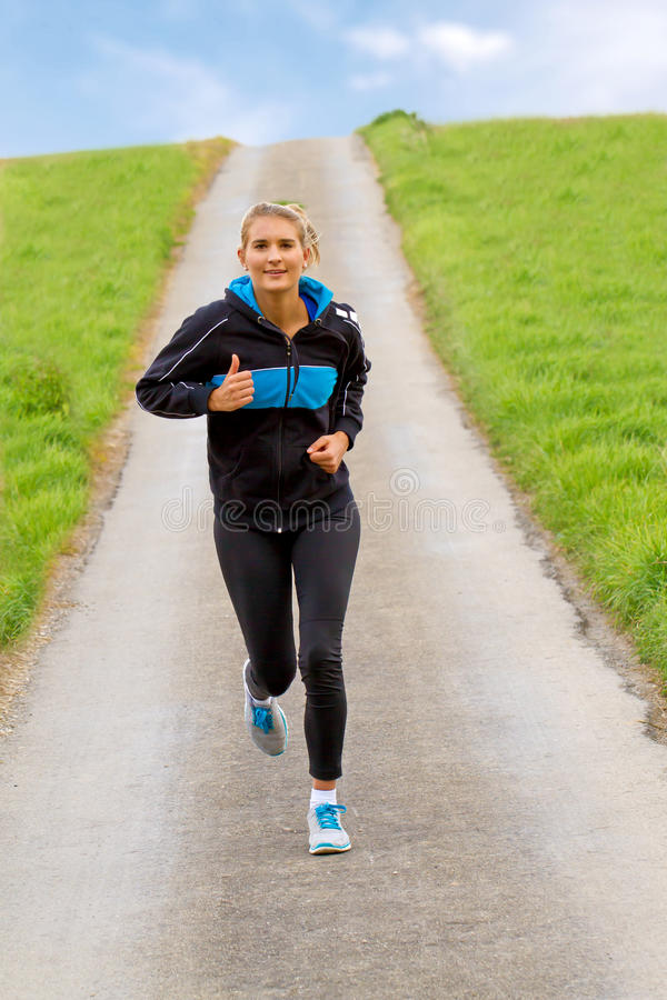 年轻愉快妇女跑步 库存图片