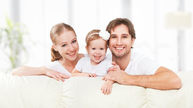 愉快家庭母亲、父亲,儿童小女儿在家使用的沙发的和笑 免版税库存图片