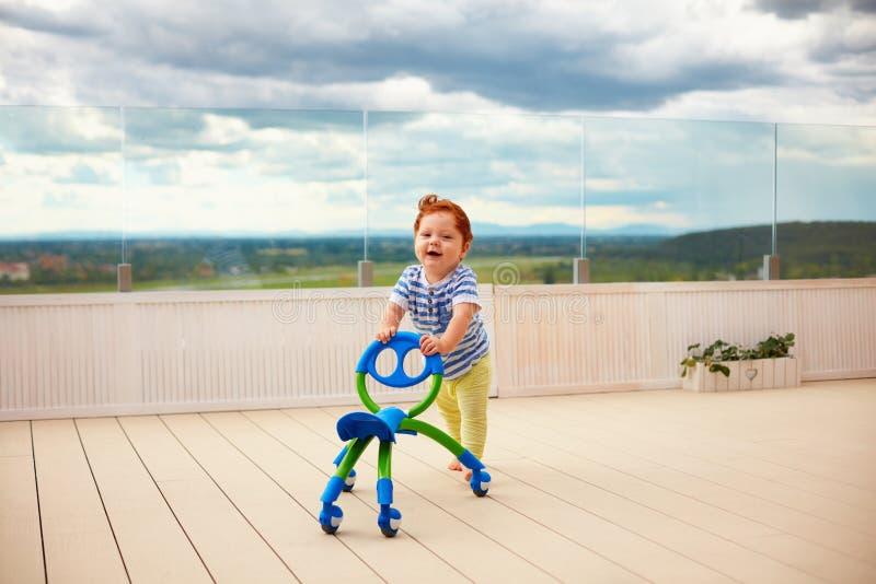 愉快小孩男婴推挤去推车,户外 库存图片