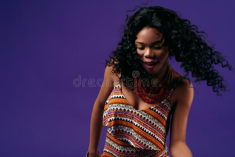 愉快年轻在淡紫色背景的黑人妇女和跳舞 免版税库存照片
