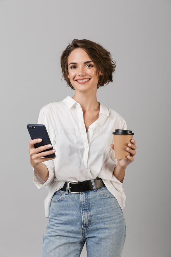 愉快年轻女商人摆在被隔绝在聊天灰色墙壁的背景由手机饮用的咖啡 免版税库存图片