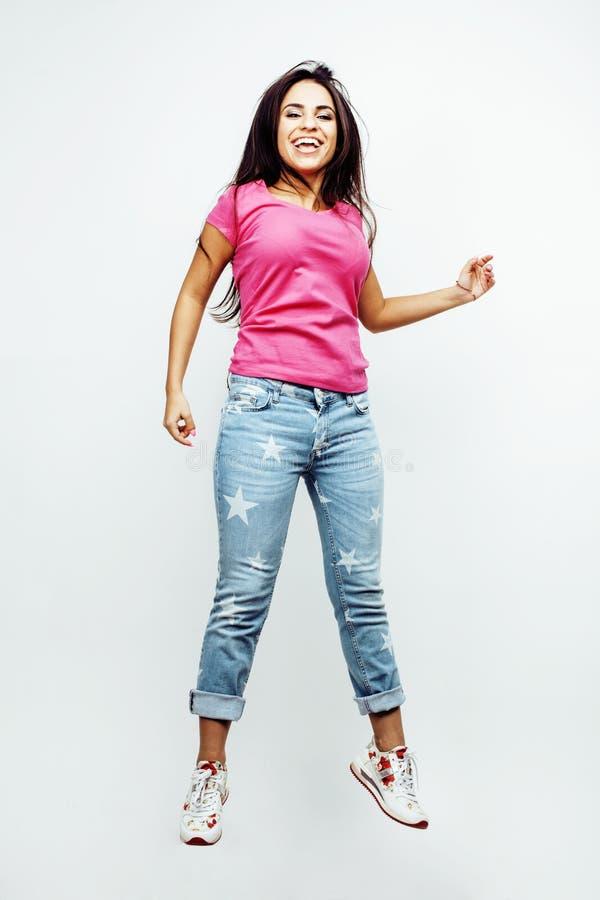 年轻愉快微笑的拉丁美洲十几岁的女孩情感摆在白色背景,在喜悦,生活方式的跳跃的飞行 免版税库存图片