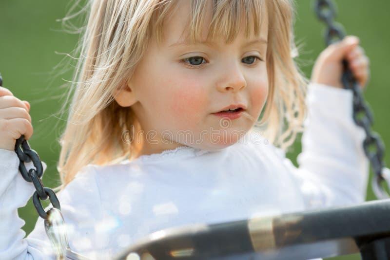 愉快微笑的年轻婴孩白种人白肤金发的真正的人女孩关闭室外使用在摇摆 图库摄影