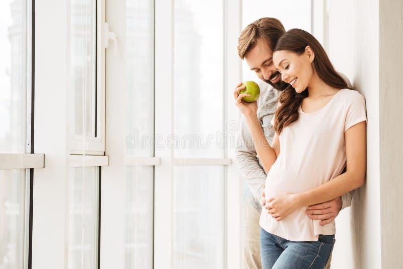 愉快怀孕年轻夫妇拥抱 免版税库存照片