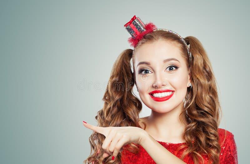 愉快时装模特儿女孩指向 有逗人喜爱的微笑和滑稽的面孔点的美丽的年轻女人 免版税库存照片