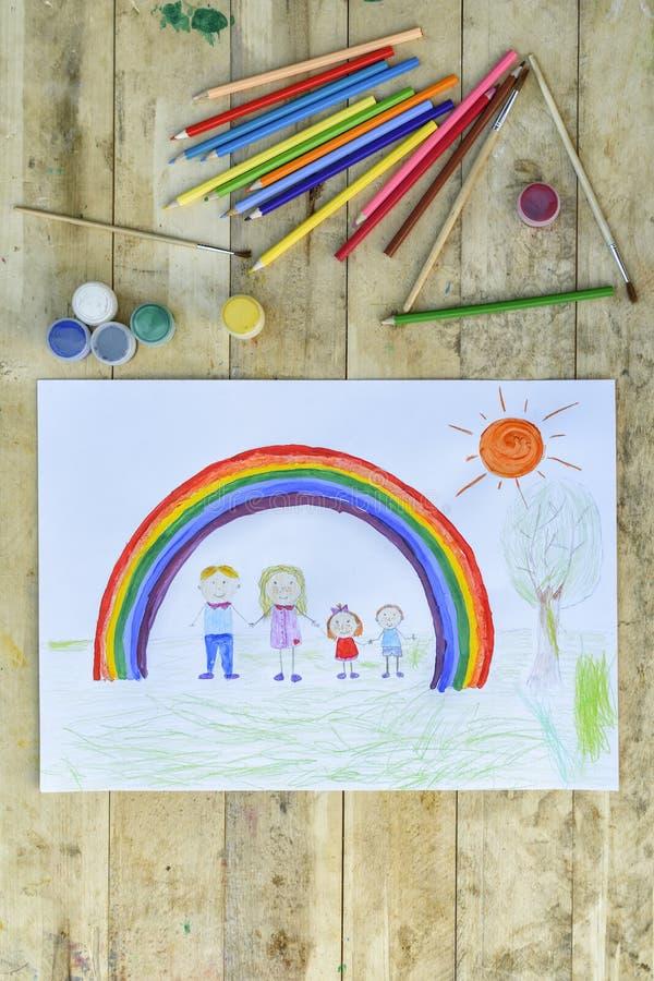 愉快概念的系列 与一个样式的板料在一张木桌上:父母和孩子握手反对彩虹背景和 皇族释放例证