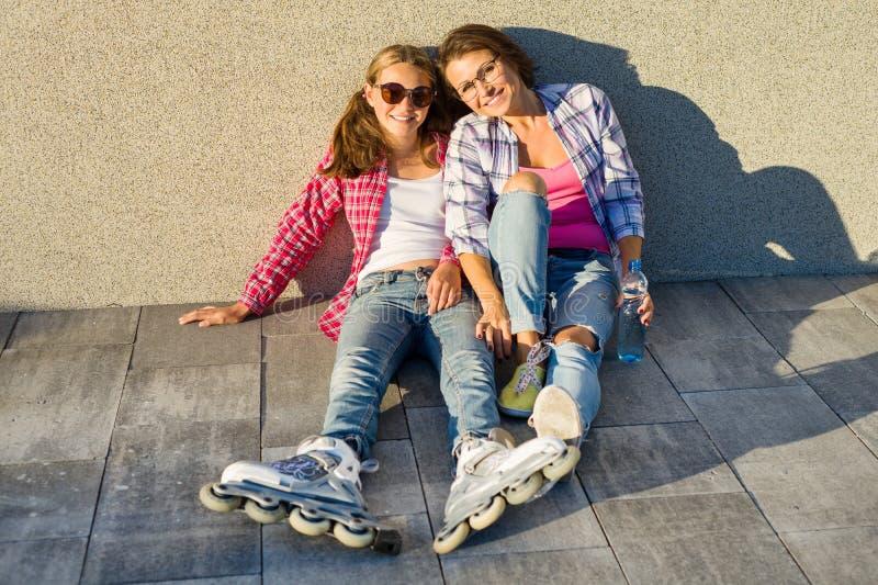 愉快母亲和女儿青少年谈话户外 免版税库存图片
