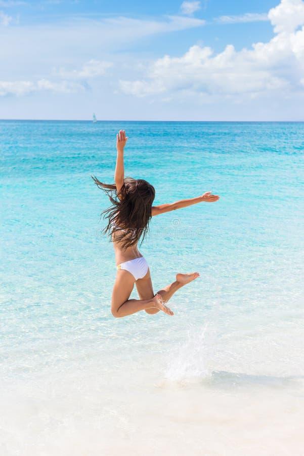 愉快海滩假期成功妇女跳跃喜悦 库存图片