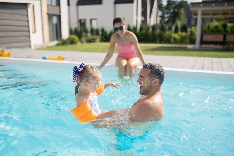 愉快父亲的感觉,当游泳与他逗人喜爱的可爱的女孩时 图库摄影