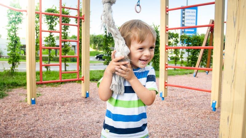 愉快特写镜头的画象可爱微笑儿童操场的小男孩在公园 免版税库存图片