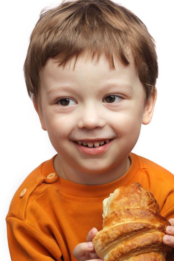 愉快男孩的新月形面包 免版税库存照片