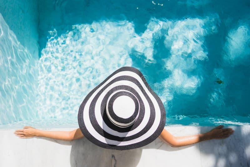 愉快画象美好的年轻亚洲妇女的微笑在旅馆手段的游泳场附近放松休闲的 免版税库存图片