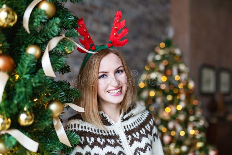 愉快的一头鹿的妇女佩带的圣诞节鹿角在圣诞树附近的 免版税图库摄影