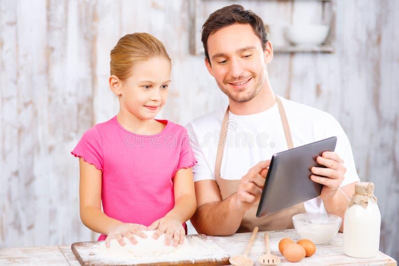 愉快的一起烘烤父亲和的女儿 免版税图库摄影