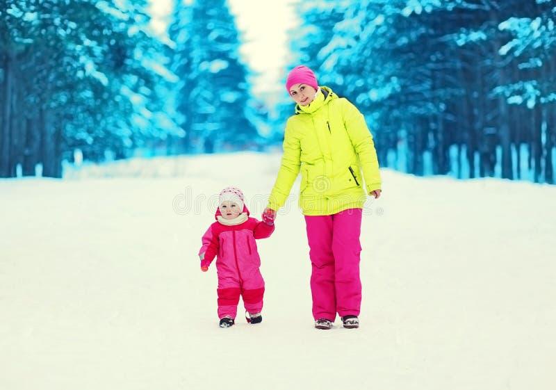 愉快的一起走在冬天森林里的母亲和婴孩 免版税库存图片