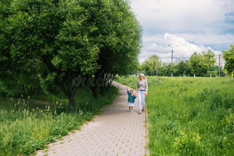 愉快的一起走在夏天公园的母亲和孩子 图库摄影