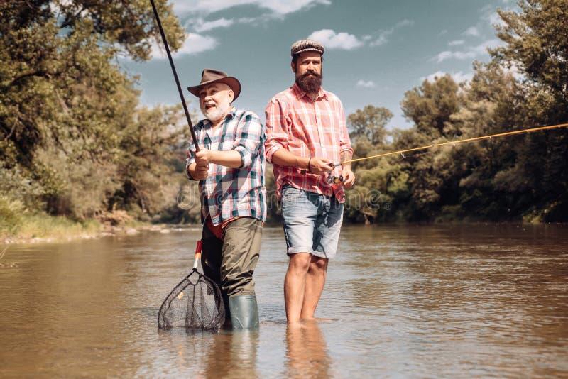 愉快的一起钓鱼在夏日的父亲和儿子在河的美丽的天空下 渔夫和战利品鳟鱼 ?? 免版税库存图片