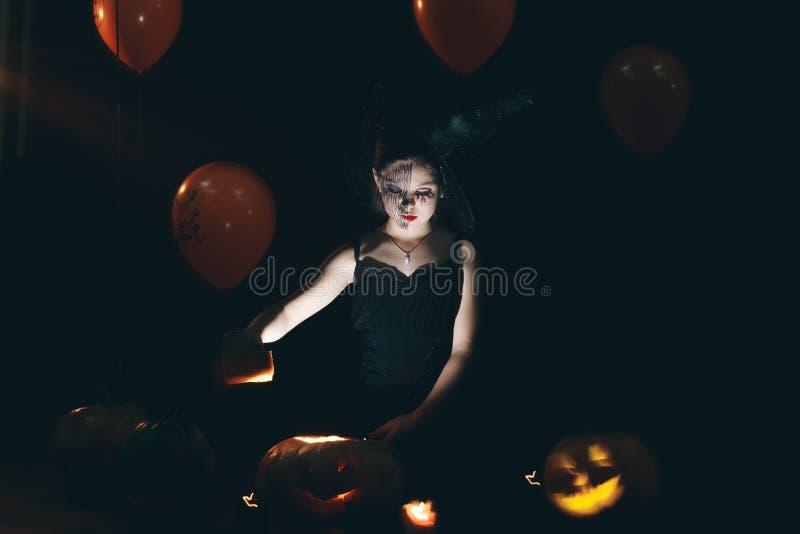 愉快的万圣夜逗人喜爱的矮小的巫婆用一个大南瓜 巫婆的美丽的幼儿女孩打扮得户外 库存图片