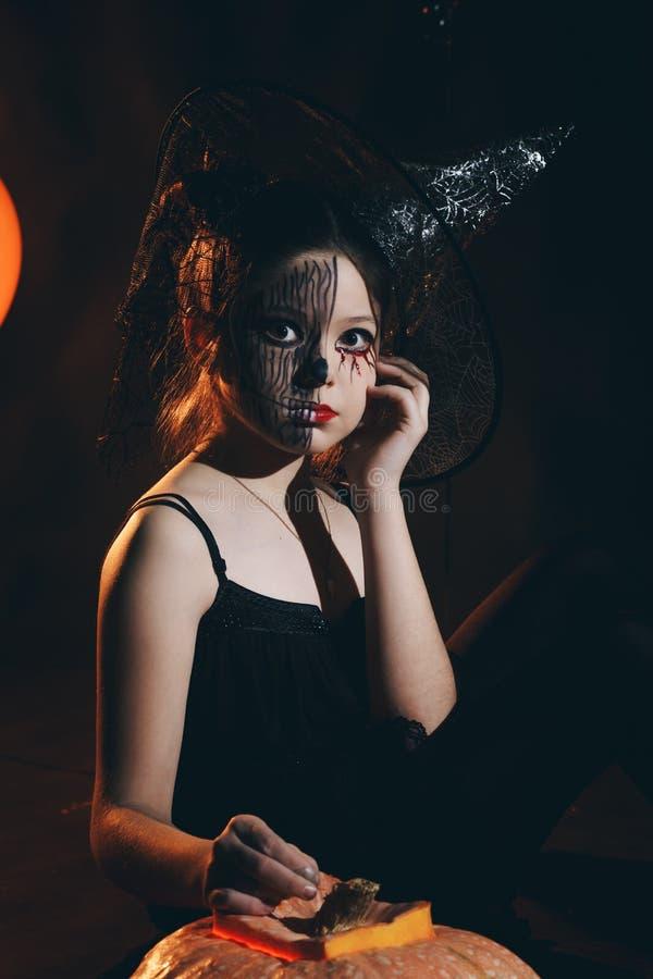 愉快的万圣夜逗人喜爱的矮小的巫婆用一个大南瓜 巫婆的美丽的幼儿女孩打扮得户外 图库摄影