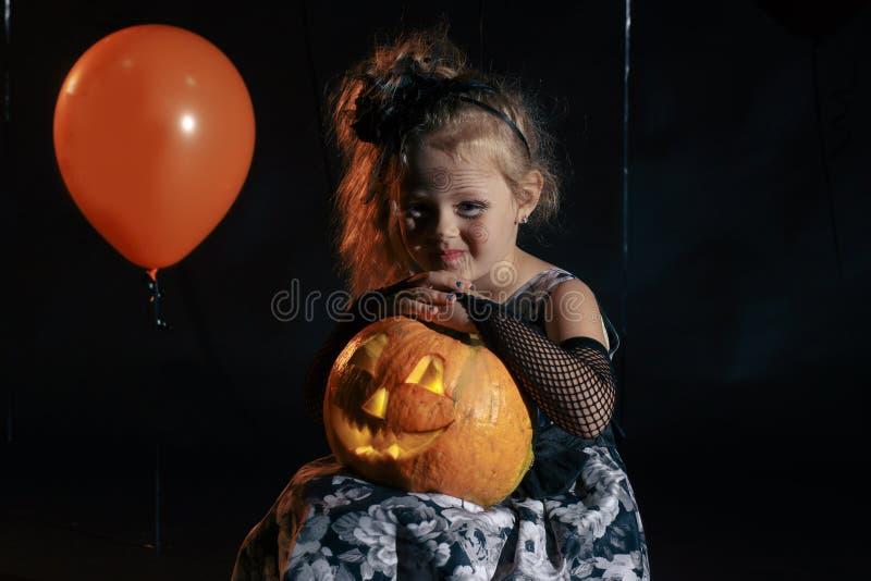 愉快的万圣夜逗人喜爱的矮小的巫婆用南瓜 免版税图库摄影