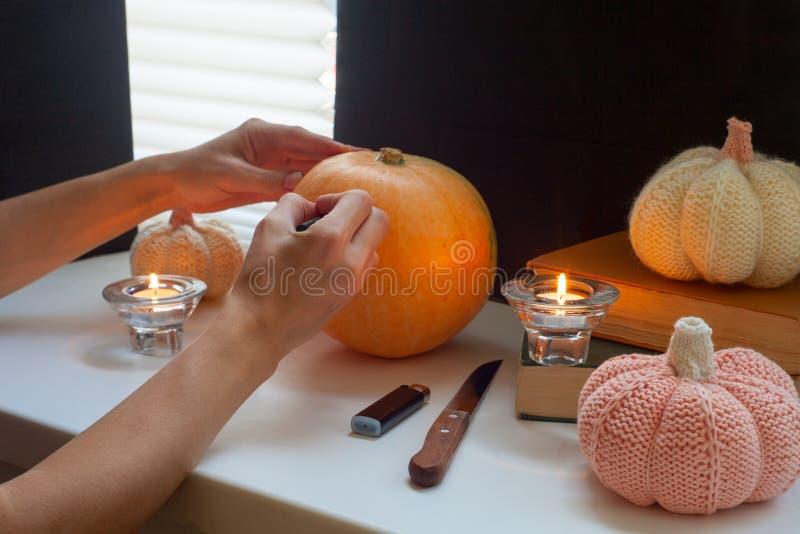 愉快的万圣夜!可爱的年轻孕妇准备对在厨房的万圣夜 美丽的妇女绘南瓜 免版税库存照片