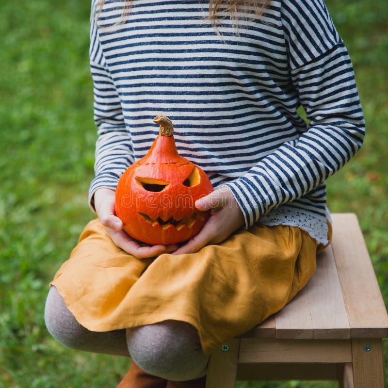 愉快的万圣节 在木椅子和举行的女孩位子户外一点南瓜杰克O灯笼 免版税库存照片