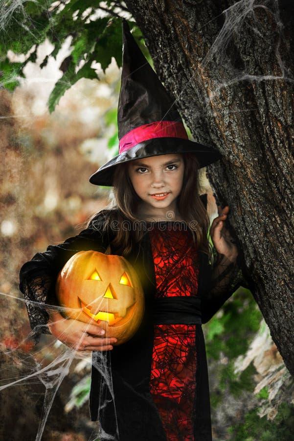 愉快的万圣节 逗人喜爱的矮小的巫婆用一个南瓜在手上 免版税库存图片