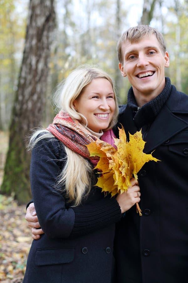 愉快的丈夫和妻子有黄色槭树leafle的笑 免版税库存照片