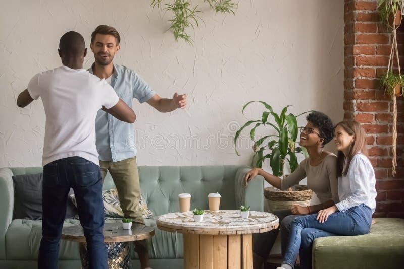 愉快的不同的男性朋友问候在团聚会议上在咖啡馆 库存图片