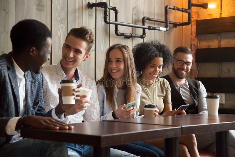 愉快的不同种族的小组朋友谈话使用智能手机在 库存图片