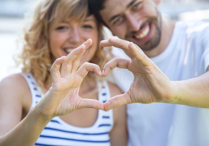 愉快的与手指的爱夫妇外部显示的心脏 免版税库存图片