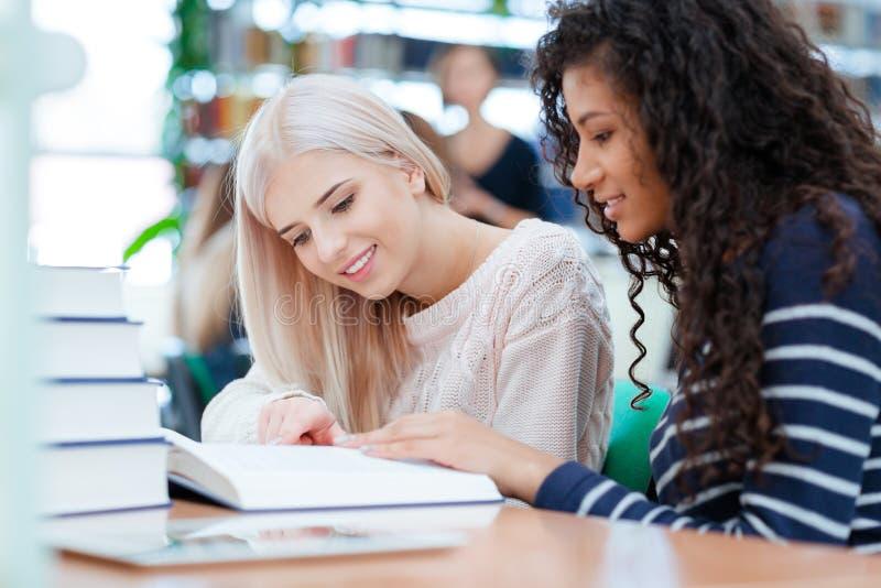 愉快的两个女孩阅读书一起 库存照片