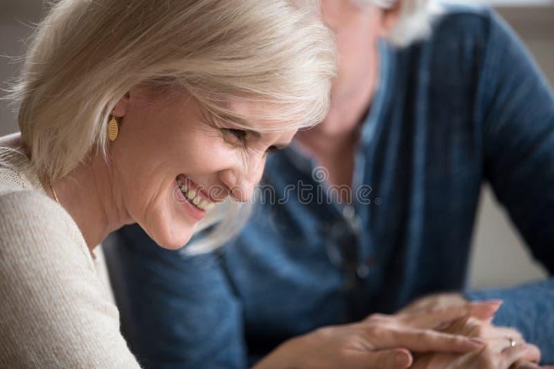 愉快的中年妇女笑的挥动与心爱的更老的人 免版税库存图片