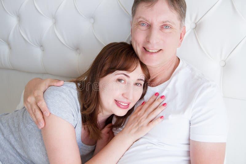 愉快的中年家庭夫妇在床上 内部白色 爱和健康关系 丈夫和妻子画象 免版税库存照片