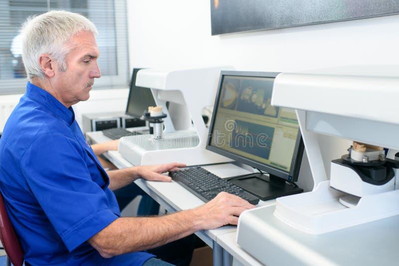 愉快的中部使用计算机的年迈的纺织品工厂劳工 免版税库存照片