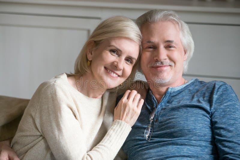 愉快的中部变老了在家拥抱浪漫的夫妇,特写po 免版税库存照片