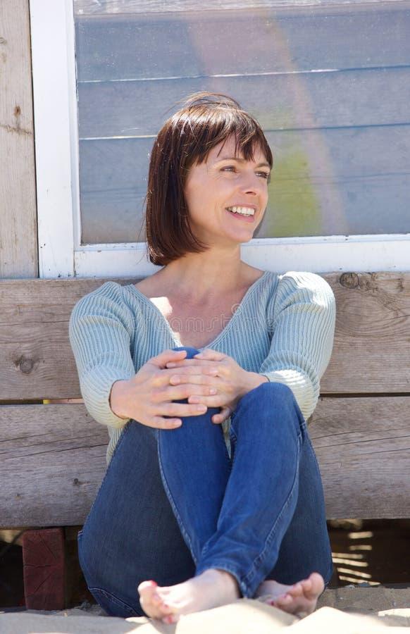 愉快的中部变老了坐的牛仔裤的妇女外面 免版税库存照片