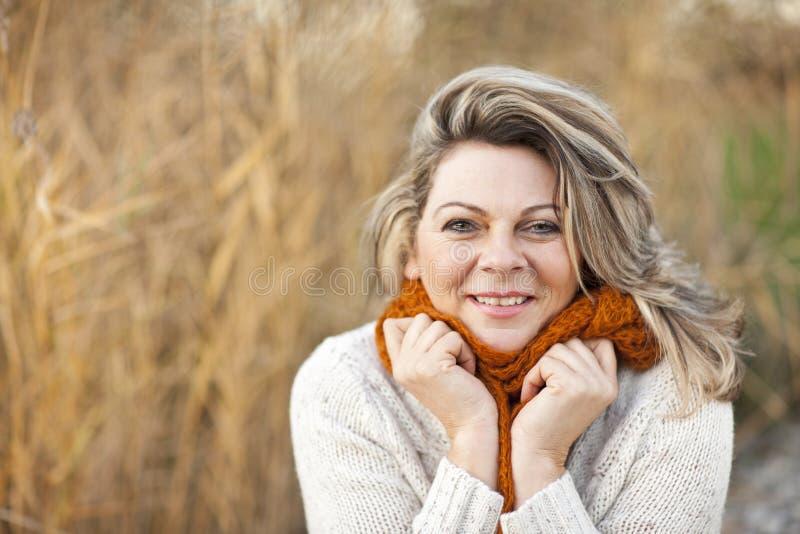 愉快的中部变老了有套头衫和围巾的妇女 图库摄影