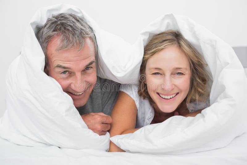 愉快的中部在鸭绒垫子下的年迈的夫妇 库存照片