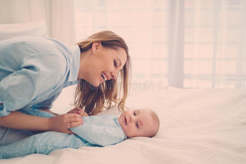 愉快的中部有她的孩子的年迈的母亲在床上 库存照片