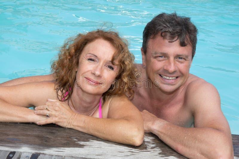 愉快的中部画象变老了放松在游泳池边缘的夫妇 库存图片