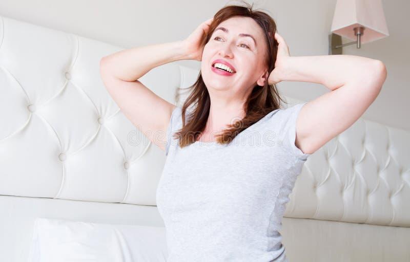 愉快的中间年迈的妇女谎言在床上 早晨好和睡眠概念 更年期和健康生活方式 r ?? 免版税库存图片