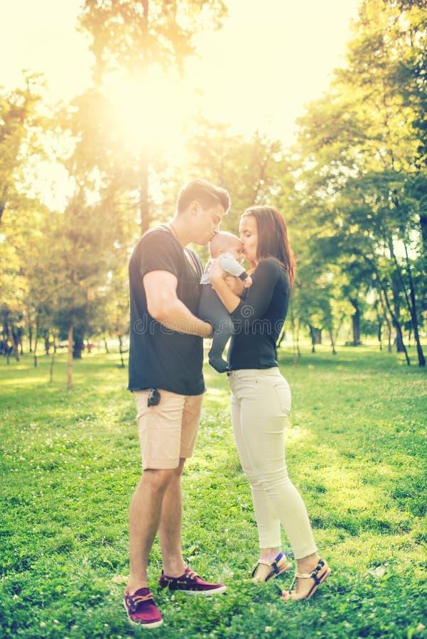 愉快的举行和亲吻一些个月儿子,孩子的家庭在公园,母亲和父亲 婴儿画象和愉快的家庭观念 免版税库存照片