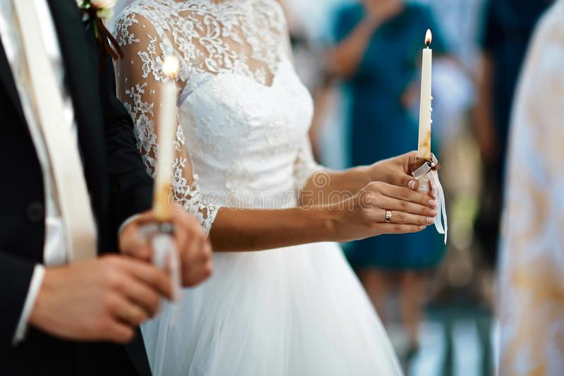 愉快的举行蜡烛婚礼,在婚姻在教会里,情感片刻,宗教的婚礼夫妇的新娘和时髦的新郎 图库摄影