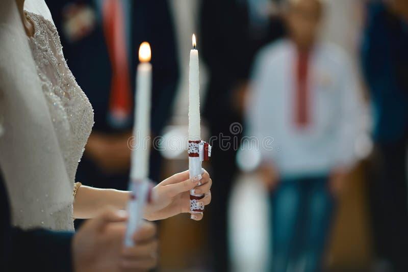 愉快的举行蜡烛婚礼,在婚姻在教会里,情感片刻,宗教的婚礼夫妇的新娘和时髦的新郎 库存照片