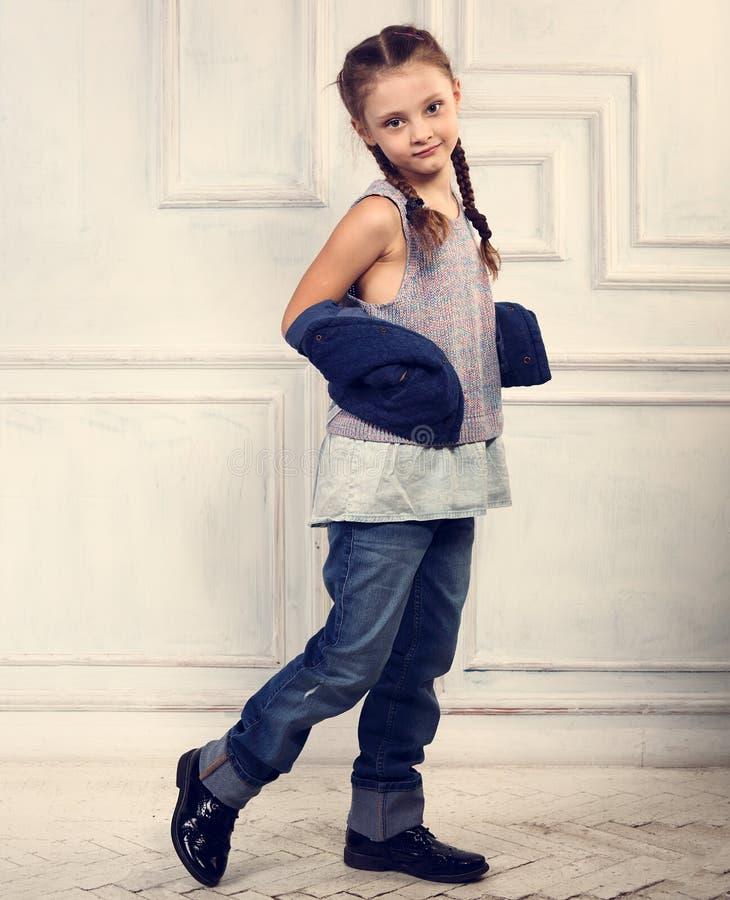 愉快的乐趣微笑的孩子女孩摆在时尚蓝色牛仔裤的,女衬衫, 库存图片