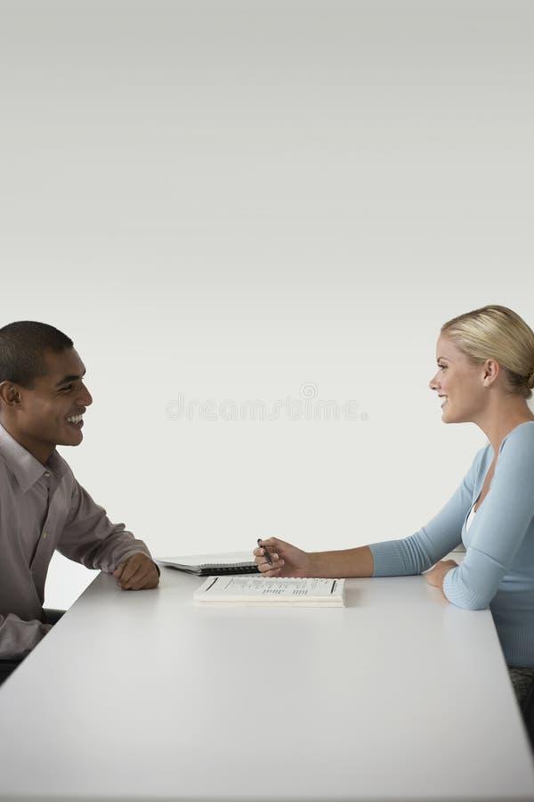 愉快的买卖人在书桌的一次会议 免版税库存照片