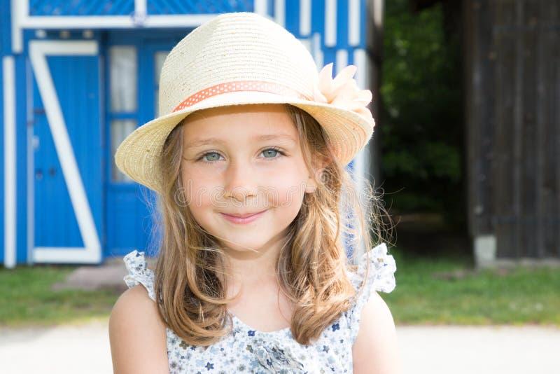 愉快的五年演奏户外与草帽的女孩特写 免版税库存照片