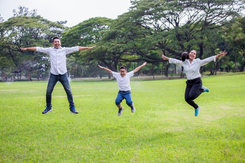 愉快的亚洲一起跳跃在公园的家庭、父母和他们的孩子 笑父亲的母亲和的儿子获得乐趣和户外 图库摄影