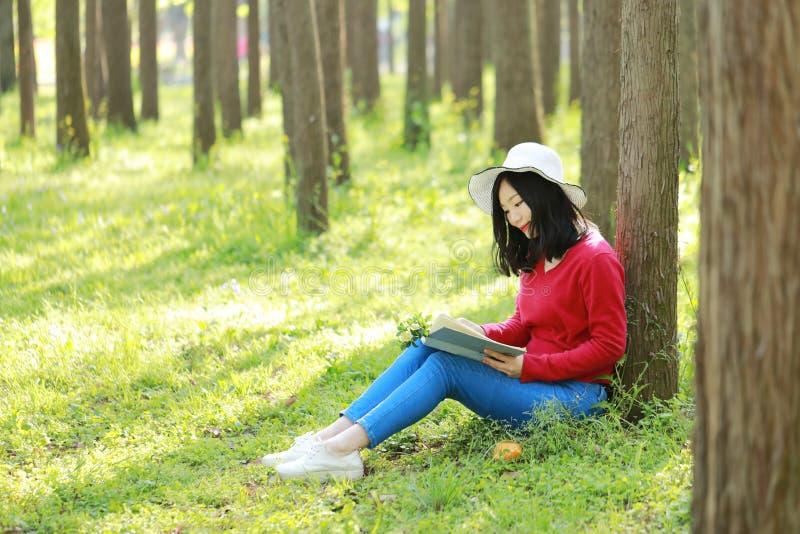 愉快的亚洲中国妇女秀丽女孩微笑和读在森林春天公园倾斜的一本书在树 图库摄影